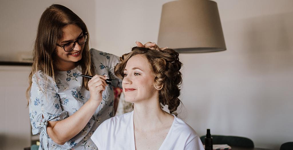 Braut wird von professioneller Visagistin geschminkt