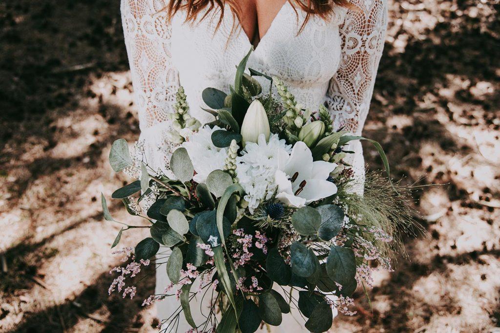Weißer Blumenstrauss in den Händen der Braut