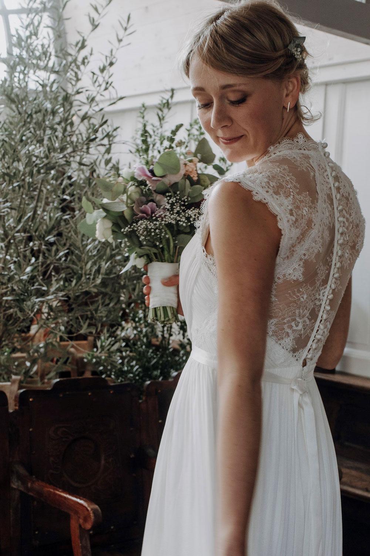 Braut vor Blumendekoration und mit Brautstrauß