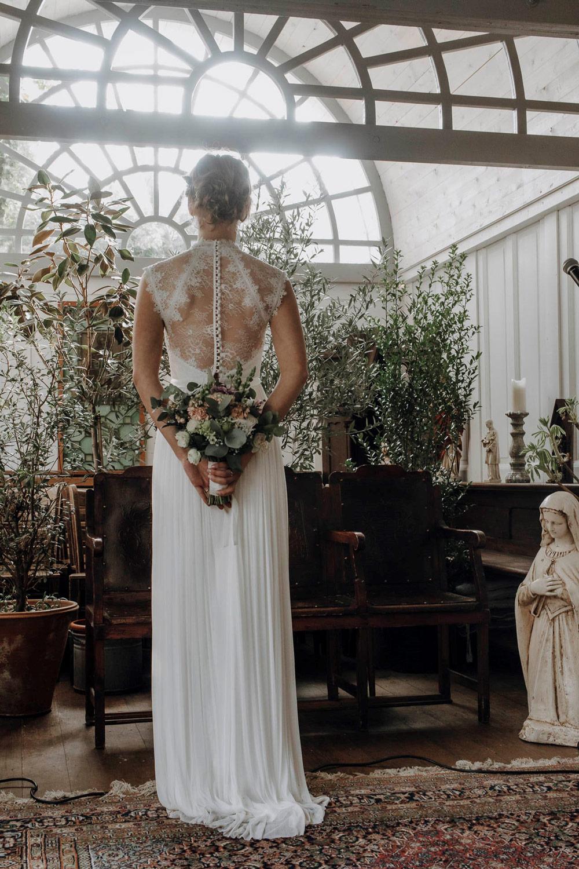 Braut vor einem Blumenarrangement in der Kapelle